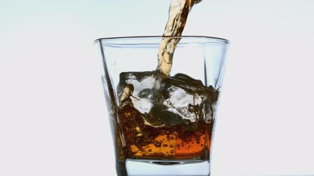 viski : Whiskey pouring into tumbler with ice in slow motion