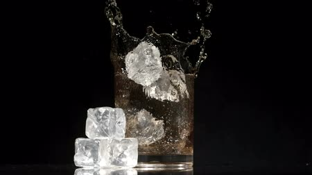 viski : Ice cubes falling into glass of whiskey and ice on black background in slow motion Stok Video