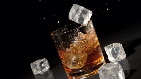 viski : Three ice cubes falling into tumbler of whiskey and ice in slow motion