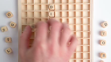 диабет : Hand spelling out diabetes message in wooden dice on grid in stop motion