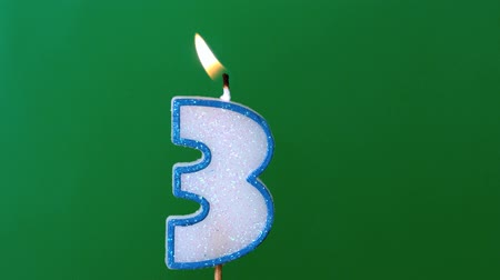 extinguishing : Three birthday candle flickering and extinguishing on green background in slow motion