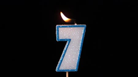 extinguishing : Seven birthday candle flickering and extinguishing on black background in slow motion Stock Footage