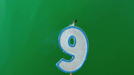 extinguishing : Nine birthday candle flickering and extinguishing on green background in slow motion
