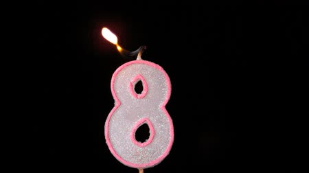 extinguishing : Eight birthday candle flickering and extinguishing on black background in slow motion