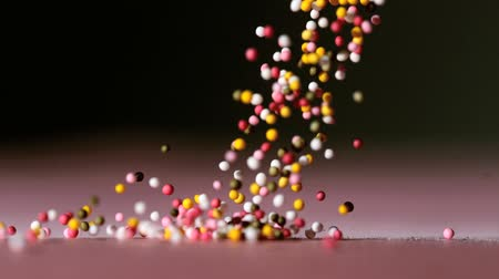 colorful candy : Sprinkles pouring onto pink surface on black background in slow motion Stock Footage