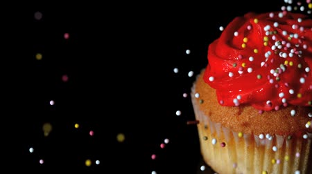 aprósütemény : Colourful sprinkles pouring onto cupcake on black surface in slow motion