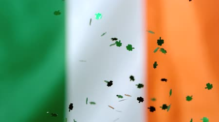 İrlanda : Shamrock confetti falling on irish flag background in slow motion Stok Video