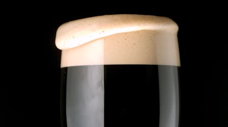 quartilho : Foam head settling on pint of stout on black background in slow motion