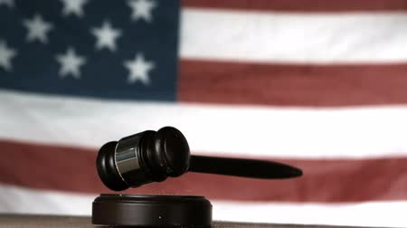 damlatma : Gavel dropping onto sounding block with american flag in background in slow motion Stok Video
