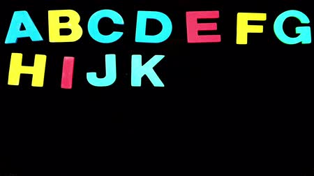 abeceda : Colourful alphabet appearing on black background in stop motion