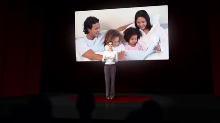 fényszóró : Animation of businesswoman in red spotlight presenting a family montage on large screen Stock mozgókép