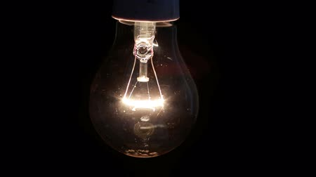 filaman : Light bulb swinging and turning off on black background Stok Video