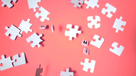 jigsaw : Plastic letters bouncing and spelling out autism next to jigsaw puzzle in slow motion