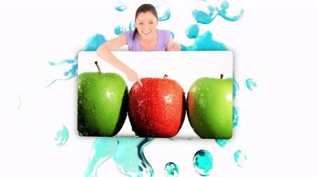 диета : Smiling woman holding a poster of fruits falling into water on white background