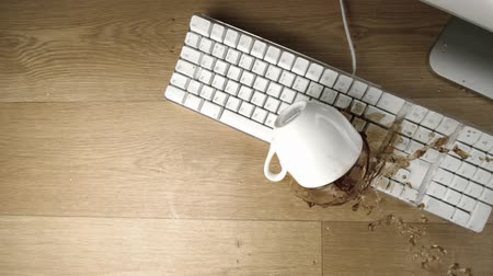 nepořádek : Cup of tea spilled out over a white keyboard in slow motion on a desk