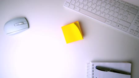 damlatma : Yellow post it falling on white office desk in slow motion Stok Video