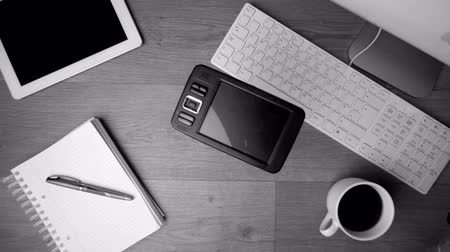 damlatma : Smartphone falling onto office desk beside computer keyboard in black and white and slow motion