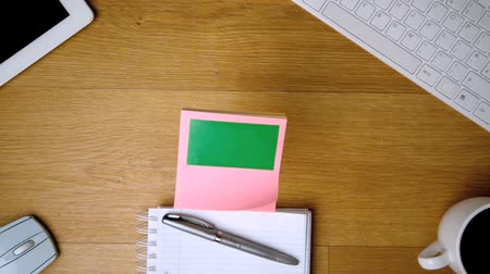 damlatma : Pink sticky notes with chroma key falling onto office desk beside notepad keyboard and tablet in slow motion
