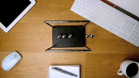 fare : Overhead of newtons cradle toy on office desk beside keyboard tablet and notebook in slow motion Stok Video