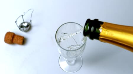 šampaňské : Champagne being poured into flute on white surface high angle view  in slow motion