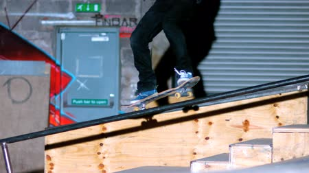 deskorolka : Skater doing crook slide down rail with graffiti wall in background in slow motion