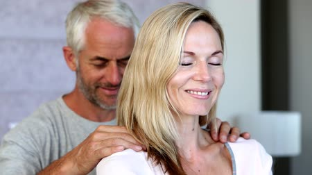 massages : Man giving partner a shoulder rub at home in the bedroom