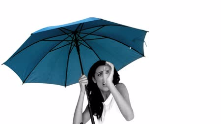 apprehensive : Woman under blue umbrella cowering with fear in slow motion Stock Footage