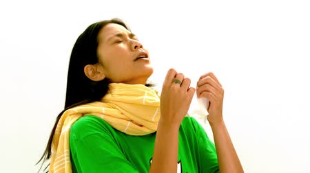chřipka : Asian woman in green tshirt and yellow scarf sneezing in slow motion on white background