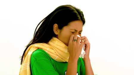 chřipka : Asian lady in green tshirt and yellow scarf sneezing against white backgroundin slow motion