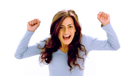 izgatott : Pretty brunette cheering with joy on white background in slow motion