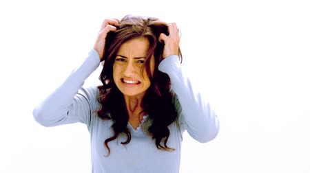 sinir : Brunette shaking head and pulling at hair with anger on white background in slow motion Stok Video