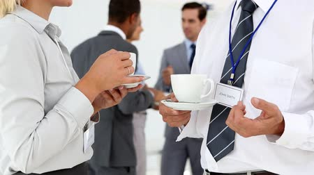 chatting : Business people chatting during coffee break with others behind them Stock Footage