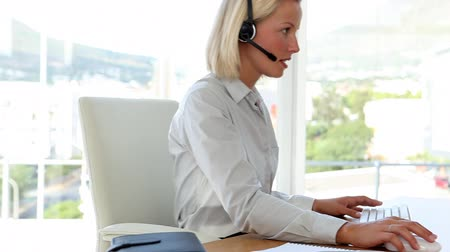 fejhallgató : Blonde haired businesswoman working with a headset in her office Stock mozgókép