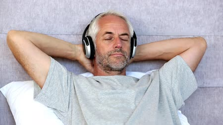 наушники : Man relaxing while listening to music with his arms behind his head in his bed Стоковые видеозаписи
