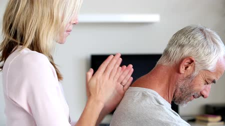 massages : Blonde woman giving an dynamic massage to her husband on his bed