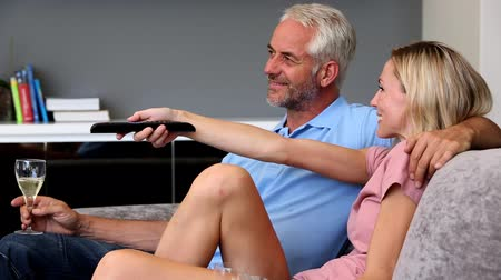 szófa : Mature couple watching television in the living room while the husband is holding a glass of white wine