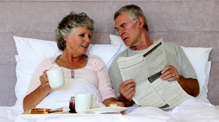 kahvaltı : Husband reading the newspaper to his wife during breakfast in bed