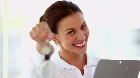 vysoká klíč : Smiling businesswoman shaking keys in front of the camera while holding a notepad