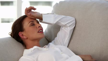 головная боль : Attractive businesswoman laid in a sofa having a nap to stop her headache