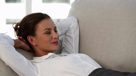 деловая женщина : Smiling businesswoman resting before going to work and lying on a sofa