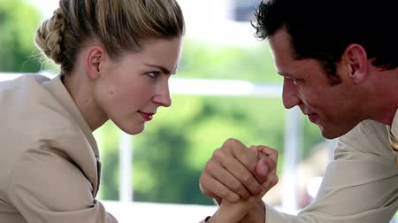 versenyképes : Businesswoman and businessman arm wrestling at the office