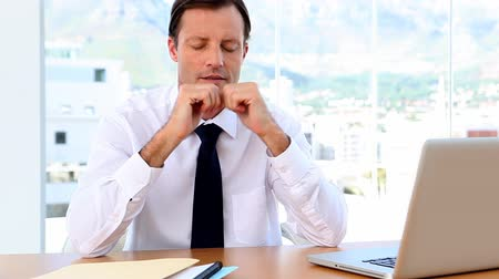 беспокоюсь : Businessman rubbing temples and looking worried sitting at desk in office
