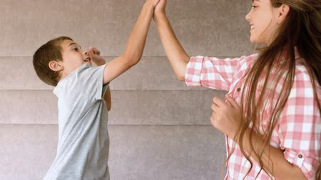 slapping : Siblings high-fiving in bedroom in slow-motion at 500 frames per second