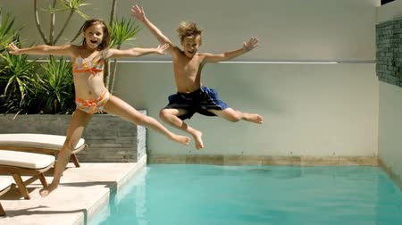 jump : Happy siblings diving into the swimming pool in slow motion at 500 frames per second Stock Footage
