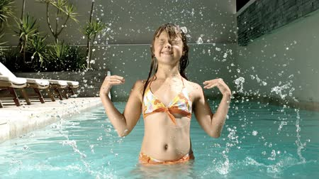 calor : Young girl splashing water in her head in the swimming pool in slow motion at 500 frames per second