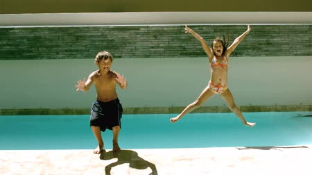 holiday villa : Siblings jumping together in the swimming pool in slow-motion at 500 frames per second Stock Footage