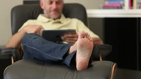 стулья : Man relaxing with his tablet sitting in recliner chair in living room Стоковые видеозаписи