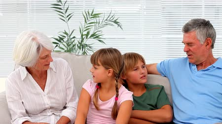 бабушка : Grandparents with grandchildren chatting sitting on the couch