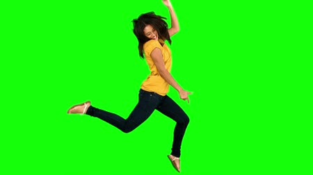 aşağı : Woman jumping on green screen in slow motion