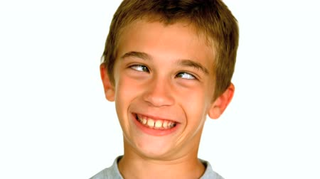 expressão facial : Little boy squinting against white background in slow motion at 250 frames per second